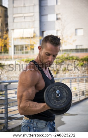 Handsome Hunk Man Lifting Weights Outdoor. Showing Healthy Body While Looking at Muscle - stock photo