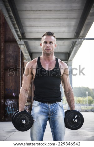 Handsome Hunk Man Lifting Weights Outdoor. Showing Healthy Body While Looking at the Camera. - stock photo
