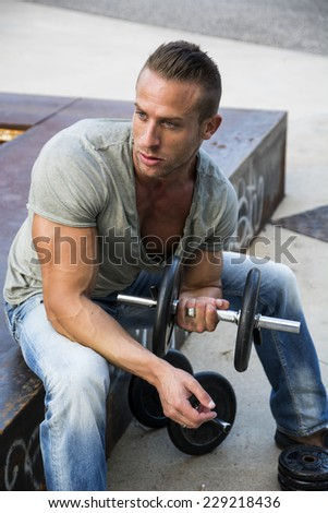 Handsome Hunk Man Lifting Weights Outdoor. Showing Healthy Body While Looking away - stock photo
