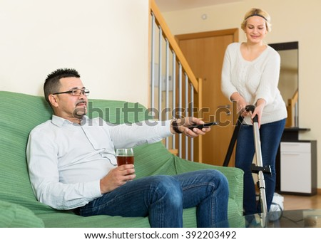 Handsome husband is sitting on a couch resting, drinking and watching a game while his smiling wife is cleaning their flat - stock photo