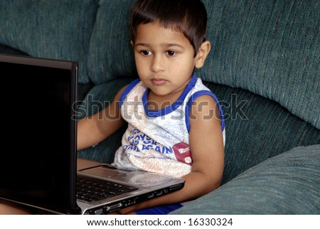 Handsome Indian kid learning using his laptop - stock photo