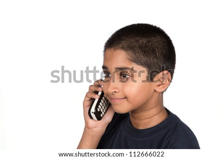 Handsome Indian kid looking very happy talking on phone - stock photo