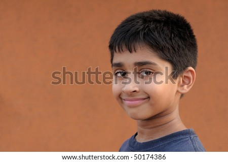Handsome Indian kid smiling in front of the camera - stock photo