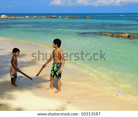 Handsome Indian kids having fun at a tropical beach with his dad - stock photo