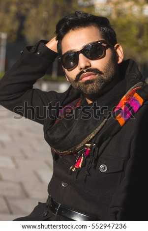 Handsome Indian man posing in an urban context. Street fashion and style.