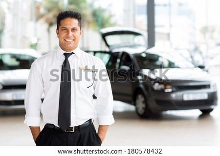 handsome indian man working at vehicle showroom - stock photo
