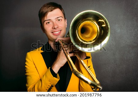 Handsome jazzer man with trombone in yellow jacket. Portrait of cheerful young musician holding trombone posing in studio - stock photo