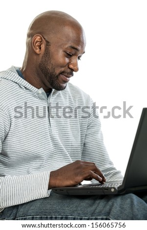 Handsome late 20s African American man typing on a laptop computer isolated on a white background - stock photo