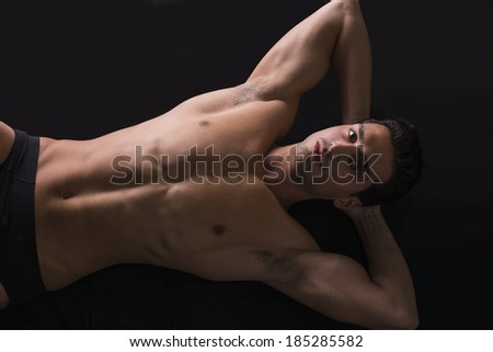 Handsome latin young man naked on floor, wearing only underwear. Muscular build - stock photo
