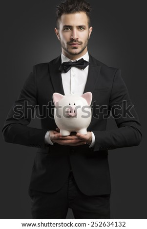 Handsome latino young man holding a piggy bank - stock photo