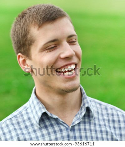 handsome laughing young man enjoying in nature