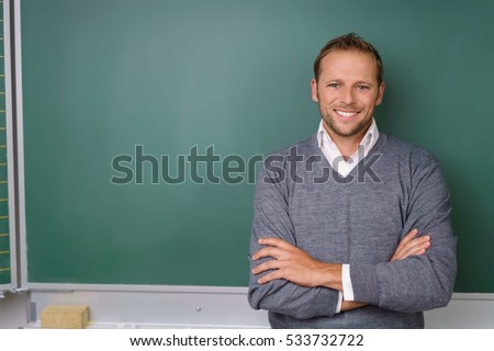 Handsome lecturer or teacher with a confident smile standing with folded arms in front of a blank chalkboard in a classroom