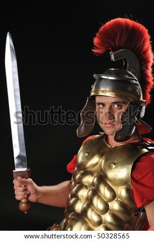 Handsome legionary soldier with a gladius - stock photo