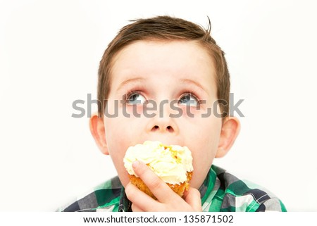 handsome little boy eating a fresh cream cup cake with messy face - stock photo