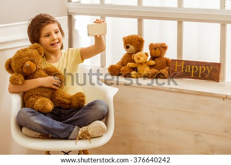 Handsome little boy hugging a teddy bear, making a photo and smiling while sitting on a chair near the window - stock photo