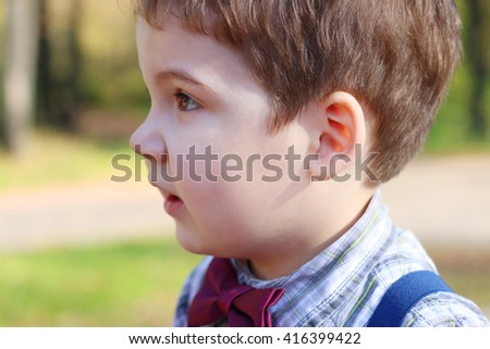 Handsome little boy in shirt and bow tie looks away in sunny green park - stock photo