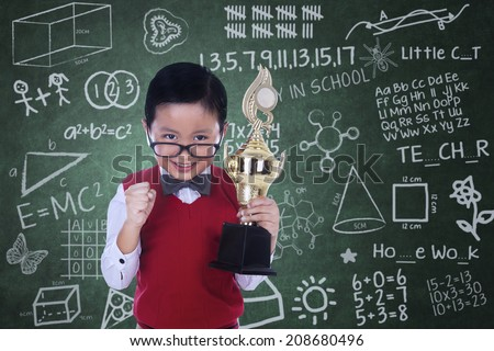 Handsome little boy is holding trophy in classroom - stock photo