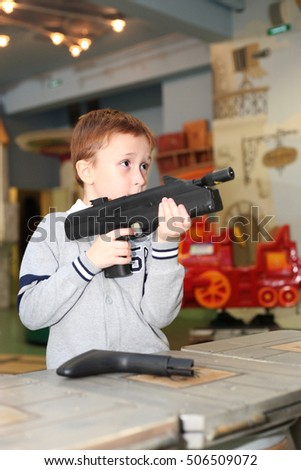 handsome little boy playing with the toy gun