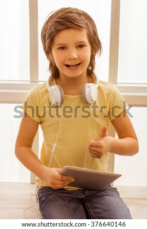 Handsome little boy using tablet, showing OK sign, looking in camera and smiling while sitting near the window - stock photo
