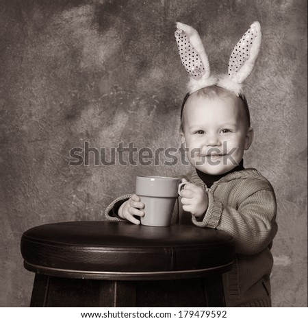 handsome little boy with hare ears studio black and white portrait - stock photo