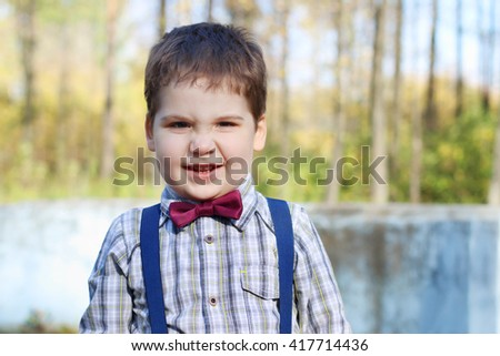 Handsome little plump boy in shirt and bow tie grimaces in sunny green park - stock photo