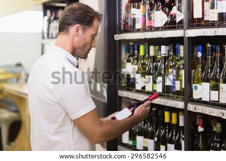 Handsome looking at wine bottle in supermarket - stock photo