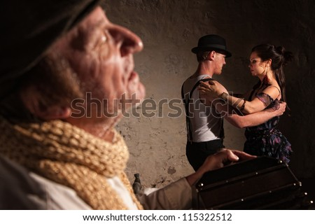 Handsome male and female tango dancers with bandonion performer - stock photo