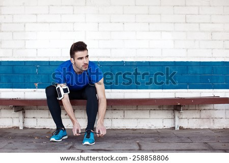 handsome male athlete sitting and tying shoelaces on the bench - stock photo