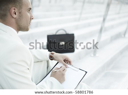 Handsome male business executive sitting on stairs outside a building with his bag - stock photo