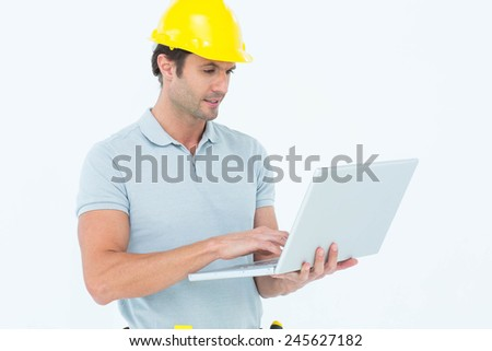 Handsome male carpenter holding laptop over white background
