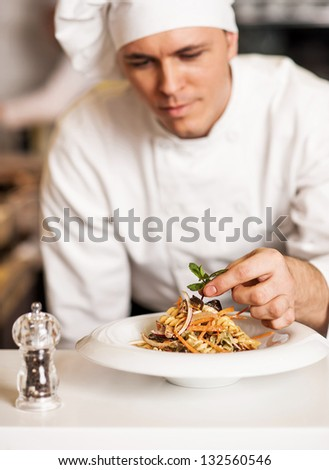 Handsome male chef dressed in white uniform decorating pasta salad. - stock photo