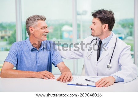 Handsome male doctor encouraging his mature patient.