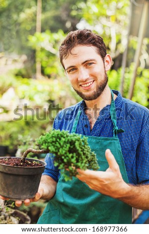Handsome male gardener with bonsai - stock photo