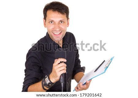 handsome male journalist reporting news on microphone with notes in hand - stock photo