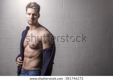 Handsome male model looking into camera - Fashionable young man against white brick background -  Sexy shirtless male model - Strong athletic and muscular - Handsome man in vest and jeans - Torso body - stock photo