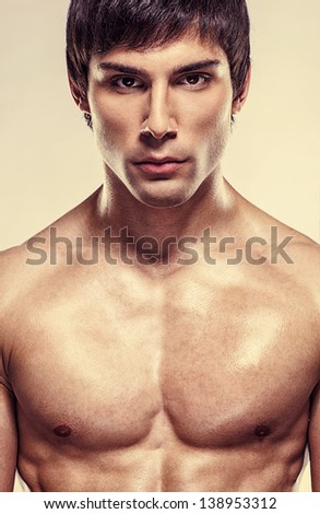 Handsome male model posing in a studio in front of a beige background. - stock photo