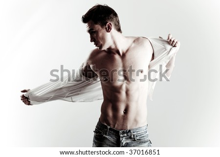 Handsome male model taking off his shirt - stock photo