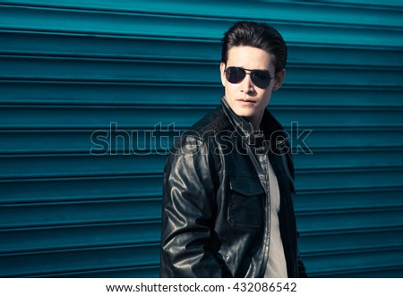 Handsome male model wearing leather jacket. - stock photo