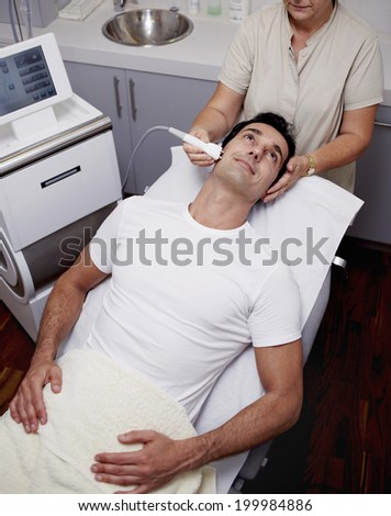 Handsome male patient dressed in the white t-shirt lying on the medical chair at facial mesotherapy looking to the female doctor in the cabinet of aesthetic clinic - stock photo