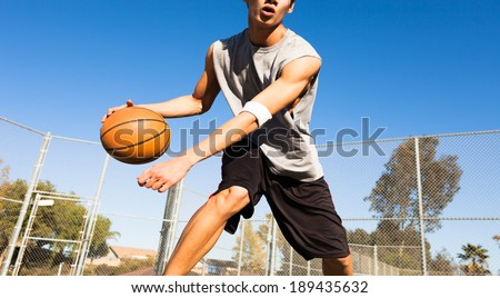 Handsome male playing basketball outdoor - stock photo