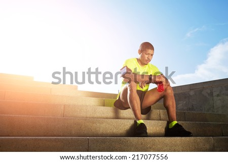 Handsome male runner very tired after run resting seated on the steps outdoors, male jogger with strong muscular body rest holding bottle of energy drink in the hands  - stock photo