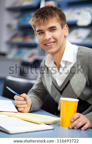 Handsome male student in a university library - stock photo