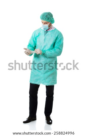 Handsome male surgeon putting on protective gloves. - stock photo