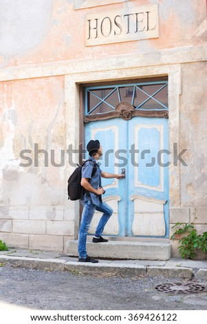 Handsome male tourist entering an old building (hostel, hotel or apartments). Traveling and couchsurfing concept.  - stock photo
