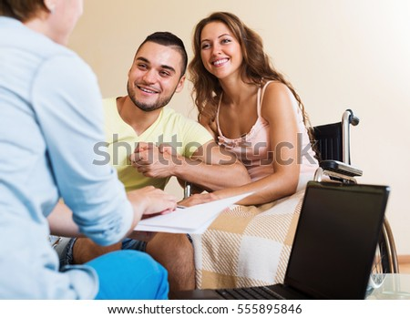 Handsome man and handicapped wife on wheelchair talking with agent