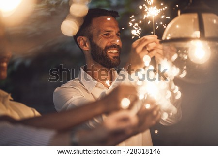 Handsome man and holding sparklers at party and smiling.