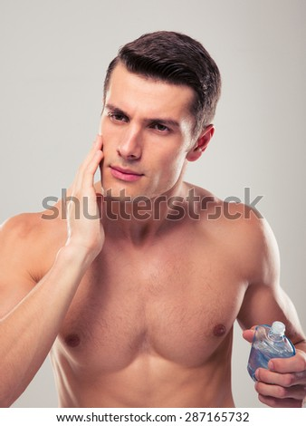Handsome man applying facial lotion over gray background - stock photo