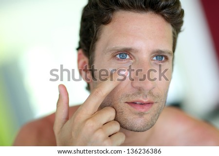 Handsome man applying moisturizing cream - stock photo