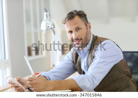 Handsome man at work using smartphone