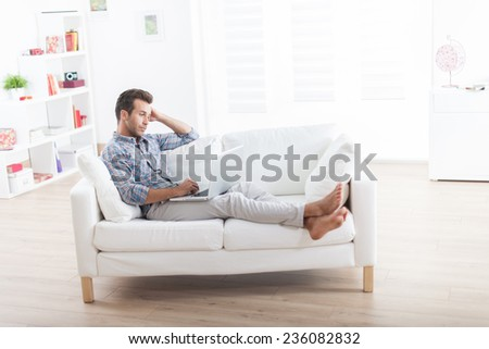 handsome man barefoot lying comfortably on a white couch and using a laptop
